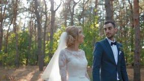 Bruid en bruidegom die in het hout lopen stock footage