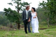Bruid en Bruidegom die in het landelijke plaatsen lopen Stock Foto's
