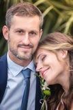 Bruid en bruidegom die in het park koesteren Stock Foto's