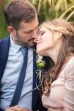 Bruid en bruidegom die in het park koesteren Royalty-vrije Stock Afbeeldingen