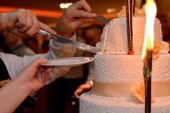 Bruid en bruidegom die hun huwelijkscake snijden royalty-vrije stock foto