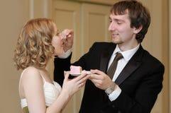 Bruid en bruidegom die huwelijkscake eten Stock Foto