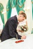 Bruid en bruidegom die huwelijksvergunning of huwelijkscontract ondertekenen Royalty-vrije Stock Foto's