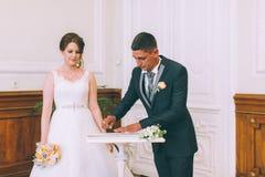 Bruid en bruidegom die huwelijksvergunning ondertekenen Stock Afbeelding