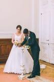 Bruid en bruidegom die huwelijksvergunning ondertekenen Stock Foto's
