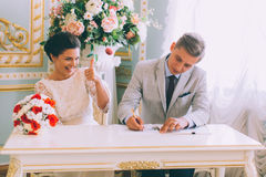 Bruid en bruidegom die huwelijksvergunning ondertekenen Royalty-vrije Stock Fotografie