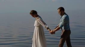 Bruid en bruidegom die langs de rivier lopen stock video