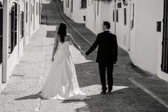 Bruid en bruidegom die langs de straat lopen royalty-vrije stock foto