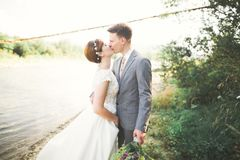 Bruid en bruidegom die mooi huwelijksboeket houden Het stellen dichtbij rivier Stock Foto's