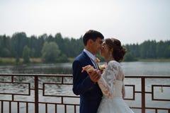 Bruid en bruidegom die op een brug dichtbij het meer omhelzen royalty-vrije stock fotografie