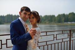 Bruid en bruidegom die op een brug dichtbij het meer omhelzen stock afbeeldingen