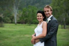 Bruid en Bruidegom die op een groen gebied koesteren Stock Afbeelding