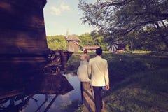 Bruid en bruidegom die op een houten brug lopen Stock Foto's