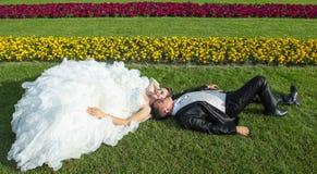 Bruid en bruidegom die op gazon liggen Royalty-vrije Stock Afbeeldingen