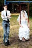 Bruid en bruidegom die op schommeling leunen Stock Fotografie