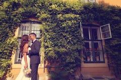 Bruid en bruidegom die in openlucht stellen Royalty-vrije Stock Fotografie