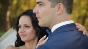 Bruid en bruidegom die in park, het kussen lopen stock videobeelden