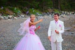 Bruid en bruidegom die pret met zeepbels hebben Royalty-vrije Stock Afbeeldingen