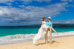 bruid en bruidegom die pret op een tropisch strand hebben Royalty-vrije Stock Afbeelding