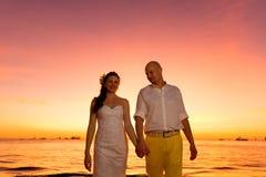 Bruid en bruidegom die pret op een tropisch strand met zonsondergang i hebben Royalty-vrije Stock Foto's