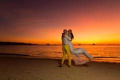 Bruid en bruidegom die pret op een tropisch strand met zonsondergang i hebben Royalty-vrije Stock Foto