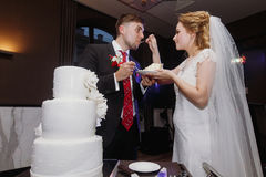 Bruid en bruidegom die samen hun modieuze huwelijkscake proeven piec royalty-vrije stock afbeeldingen