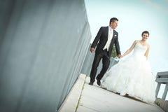 Bruid en bruidegom die in stad lopen Stock Afbeeldingen