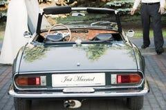 Bruid en bruidegom die zich door huwelijksauto bevinden stock afbeelding