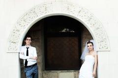 Bruid en bruidegom die zich onder witte boog bevinden Stock Fotografie