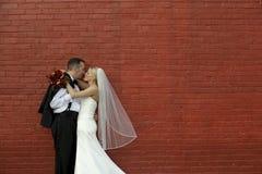 Bruid en Bruidegom door Bakstenen muur Royalty-vrije Stock Afbeelding