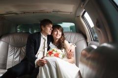 Bruid en bruidegom in een auto Stock Afbeelding