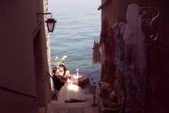 Bruid en bruidegom het kussen dichtbij oceaan Royalty-vrije Stock Afbeeldingen