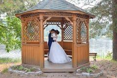 Bruid en bruidegom het kussen insude de zomerhuis royalty-vrije stock afbeeldingen
