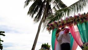 Bruid en bruidegom het kussen onder het vallen nam bloemblaadjes dichtbij huwelijksboog toe stock footage