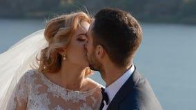 Bruid en bruidegom het stellen dichtbij de rivier stock footage