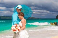 bruid en bruidegom met blauwe paraplu en huwelijksboeketten  Stock Afbeelding
