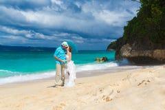 Bruid en bruidegom met blauwe paraplukus op de tropische kust Royalty-vrije Stock Foto