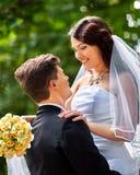 Bruid en bruidegom met bloem openlucht Royalty-vrije Stock Afbeeldingen
