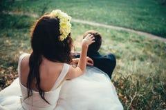 Bruid en bruidegom met bloemkroon in een bos Stock Afbeelding