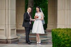 Bruid en bruidegom met een boeket van het lopen in het de zomerpark stock foto's