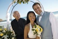 Bruid en Bruidegom met priester onder overwelfde galerij Royalty-vrije Stock Afbeeldingen