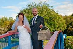 Bruid en bruidegom op brug Stock Afbeeldingen