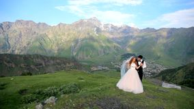 Bruid en bruidegom op de achtergrond van een prachtig berglandschap georgië Kazbegi Huwelijksphotosession stock footage