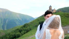 Bruid en bruidegom op de achtergrond van een prachtig berglandschap georgië Kazbegi Huwelijksphotosession stock video