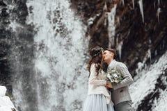 Bruid en bruidegom op de bergwaterval Royalty-vrije Stock Foto