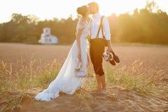 Bruid en bruidegom op een strand bij zonsondergang Royalty-vrije Stock Foto's