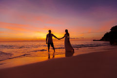 Bruid en bruidegom op een tropisch strand met de zonsondergang in backg Stock Fotografie