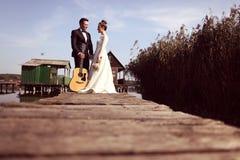 Bruid en bruidegom op houten brug dichtbij huizen op meer Royalty-vrije Stock Foto's
