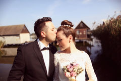 Bruid en bruidegom op houten brug dichtbij huizen op meer Royalty-vrije Stock Foto