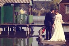 Bruid en bruidegom op houten brug dichtbij meer Royalty-vrije Stock Foto's